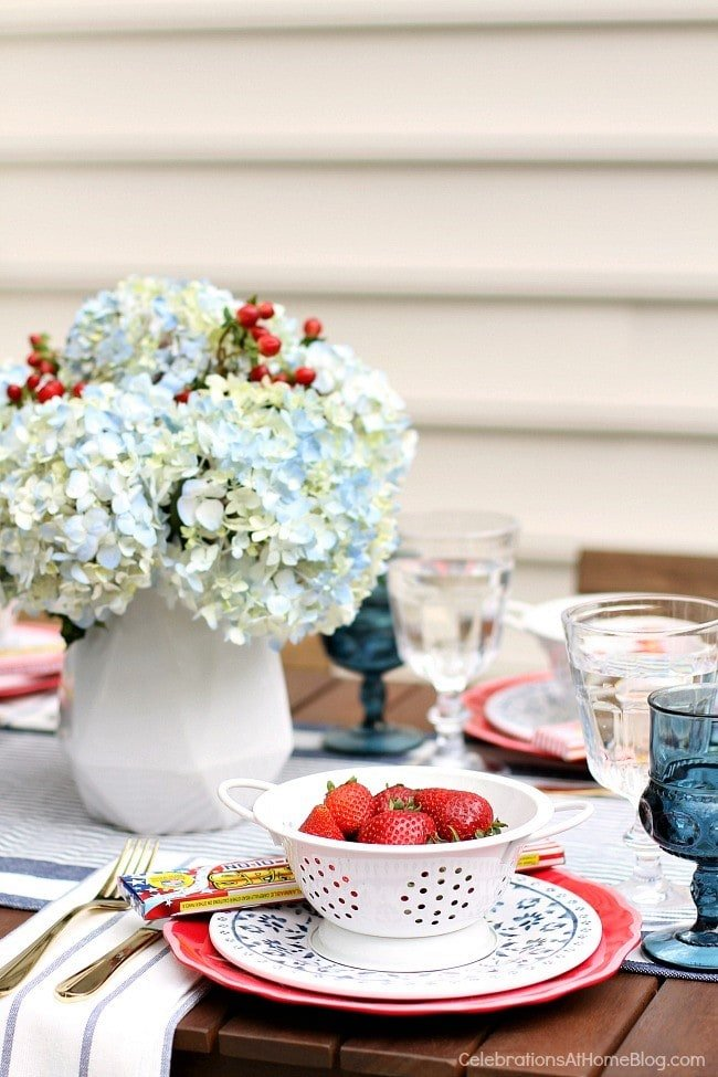A table topped with a vase of flowers and fourth of July decor