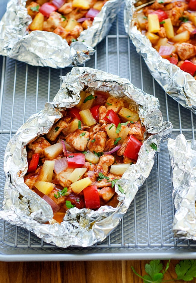 Foil packets with pineapple, chicken and peppers in them. A silver sheet pan and wire rack.