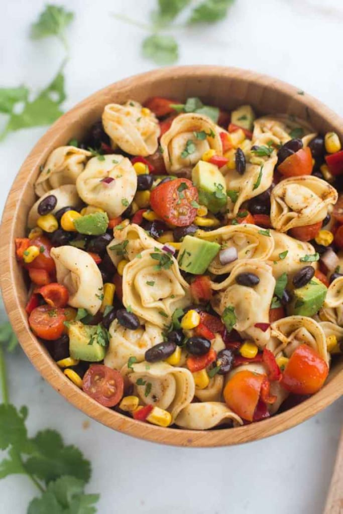 a wood bowl with tortellini, black beans, corn and tomatoes