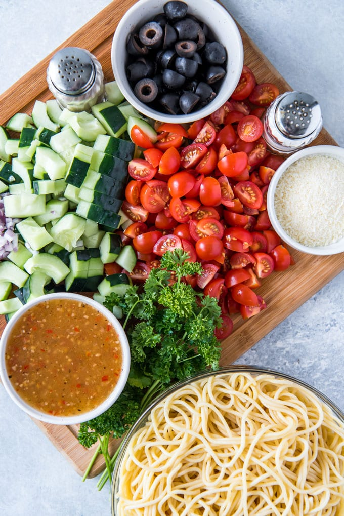 a wood cutting board, a gray background, a bowl of cooked spaghetti noodles, small bowls of Italian dressing, parmesan cheese and olives, chopped tomatoes and cucumbers, parsley and salt and pepper shakers.
