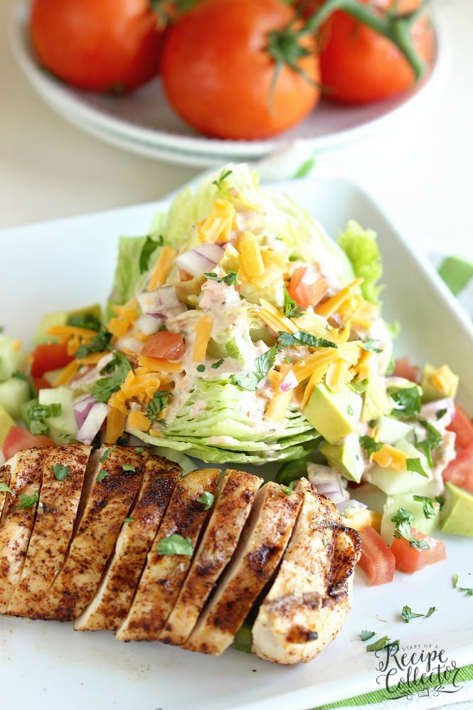 a white plate with sliced chicken and an iceber wedge salad with cheese and tomatoes and dressing. Ripe tomatoes on a stack of 2 plates.