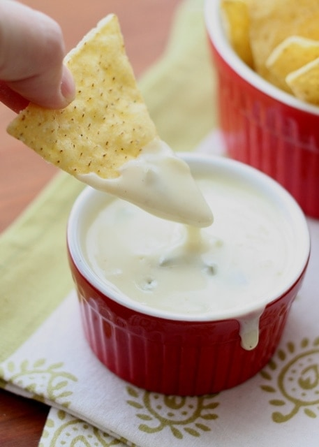A close up of a chip dipped in Queso blanco