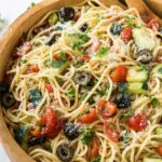 A bowl of spaghetti, olives, and tomatoes.
