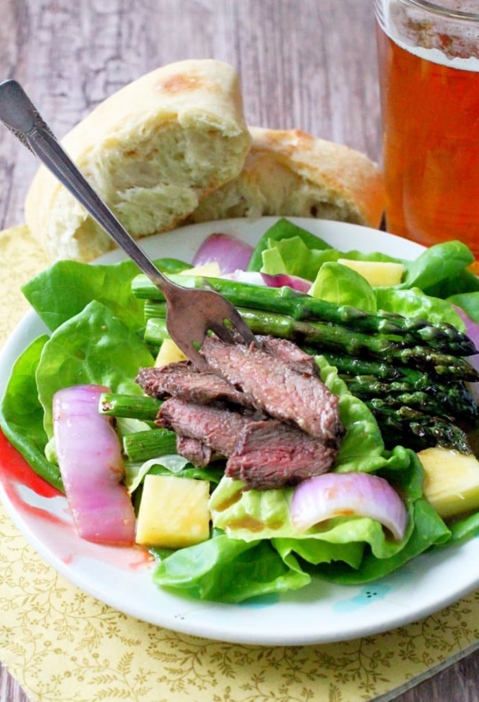 a small white plate with lettuce, onions, asparagus and sliced steak. A glass with tea and a piece of bread.