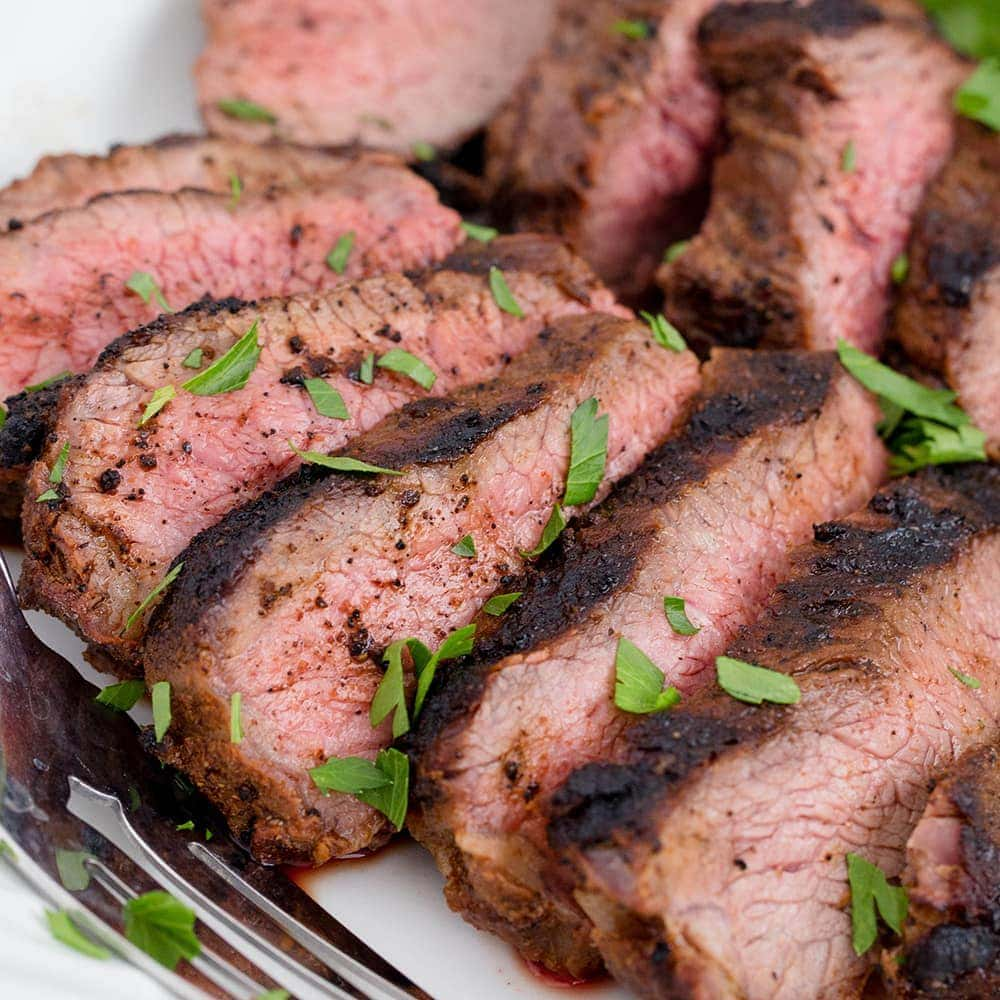 A Tri-tip steak sliced in pieces on a plate
