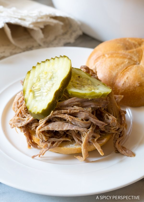 A plate of pulled pork on a bun