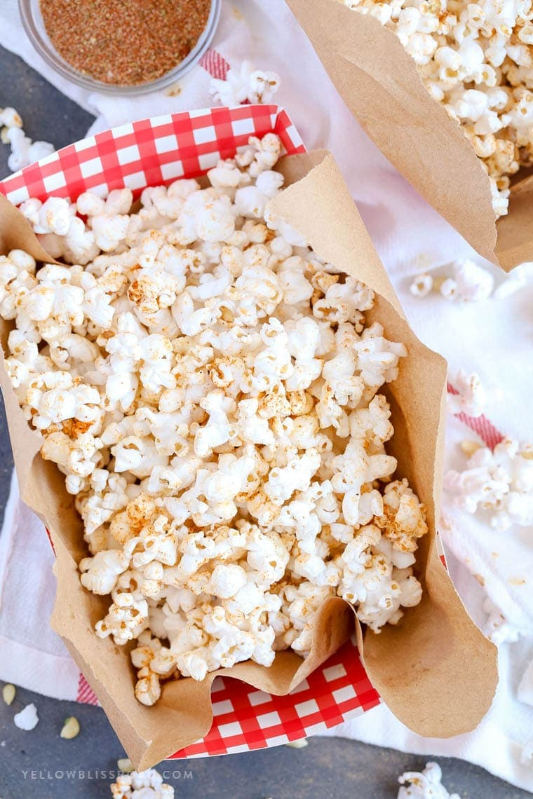 Hot Buttered Cajun Popcorn made with a Homemade Cajun Seasoning Blend in a red and white gingham bowl