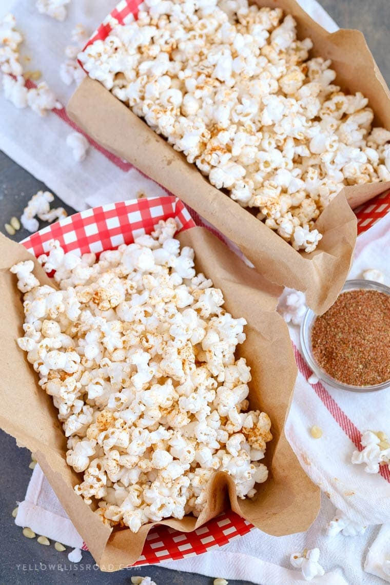 Hot Buttered Cajun Popcorn with homemade cajun seasoning in cute red and white containers.