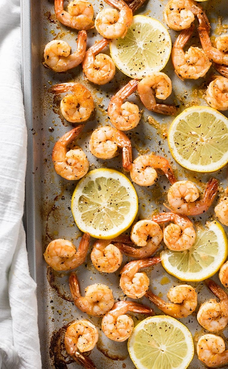 Half of a sheet pan with many shrimp with lemon pepper and lemon slices