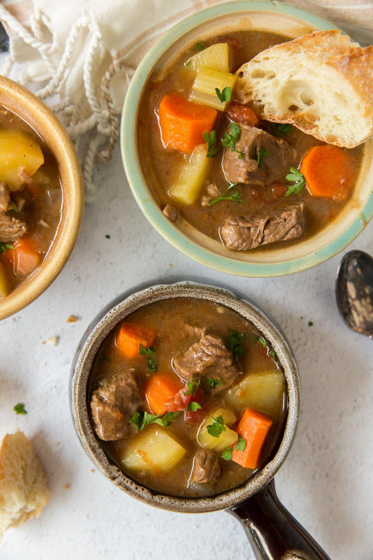 bowls with beef stea, white napkin, spoon, bread