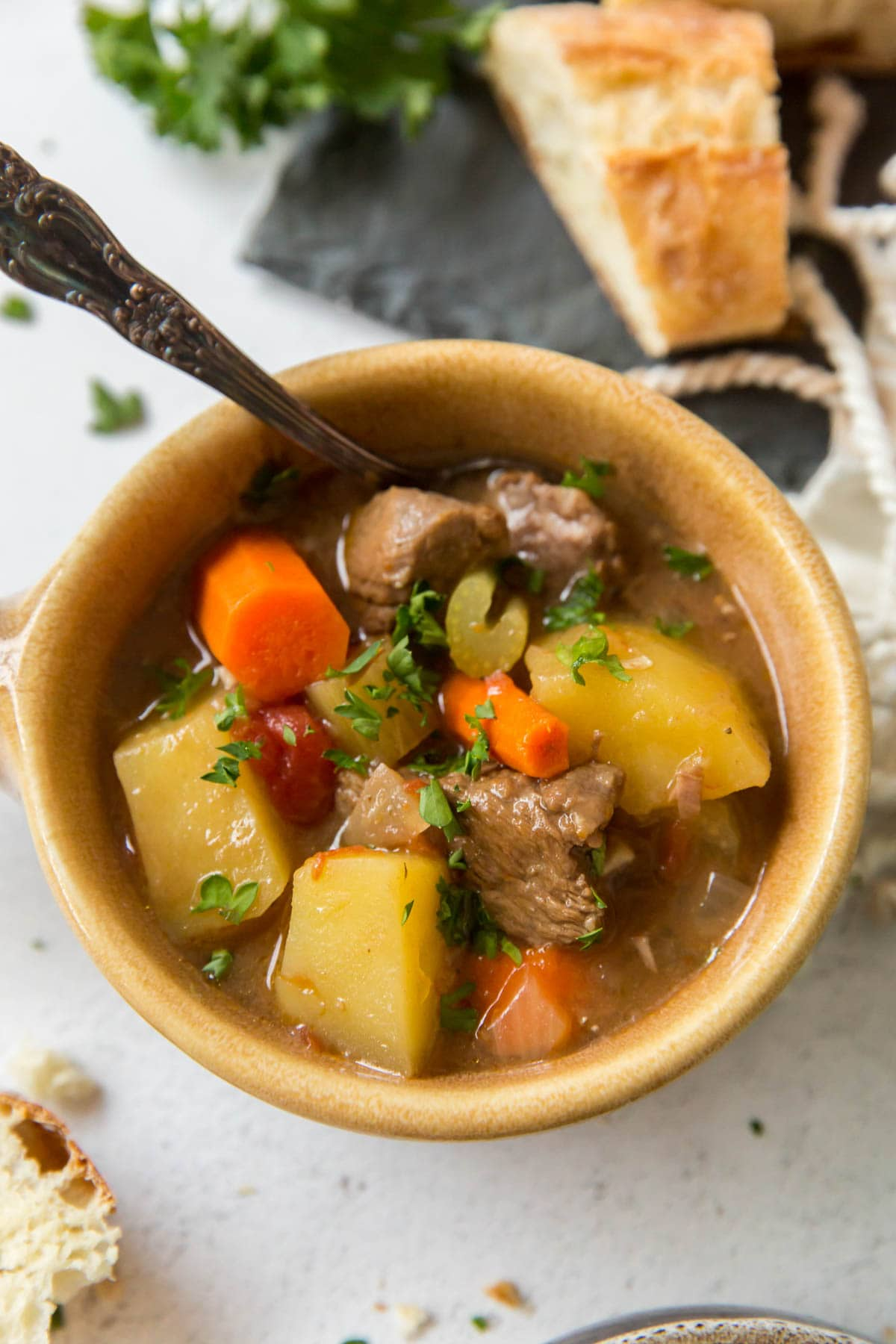 yellow bowl, spoon, parsley, bread, beef stew