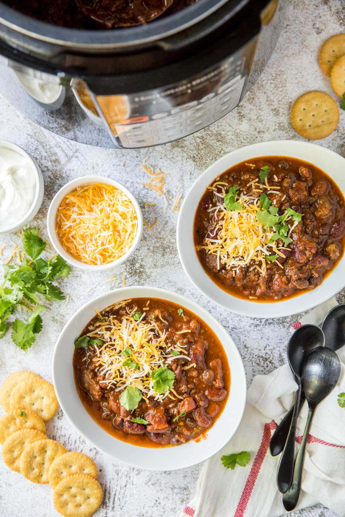 white bowls, chili, cheese, crackers, spoons, instant pot, cilantro