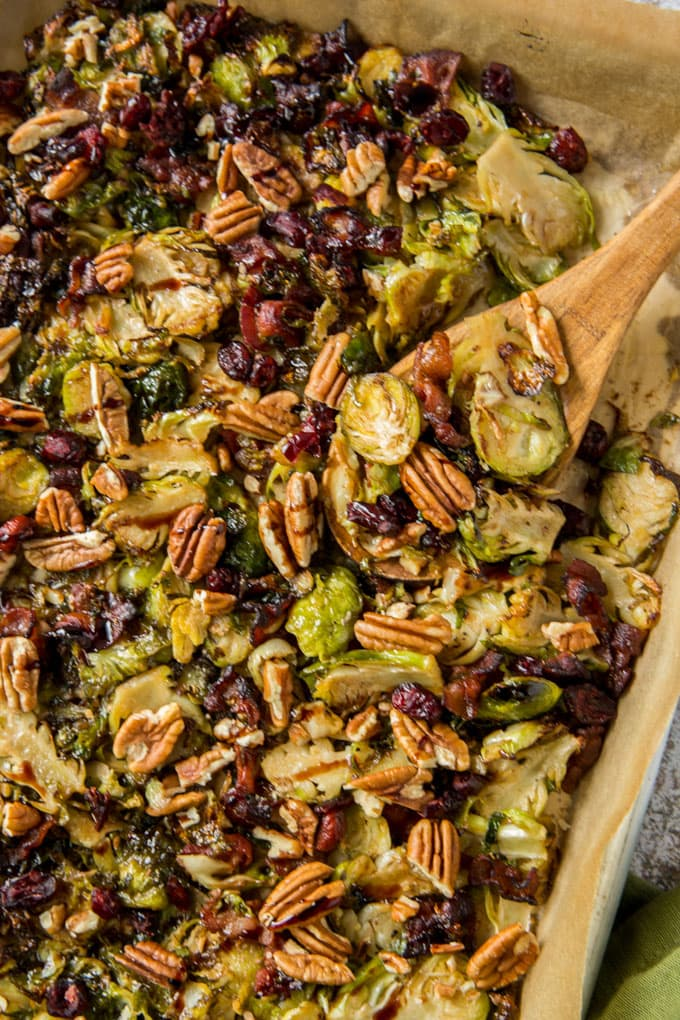 A pan of roasted brussels sprouts with cranberries, pecans and bacon