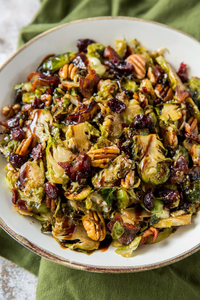 Brussels Sprouts, cranberries, pecans and bacon in a white bowl