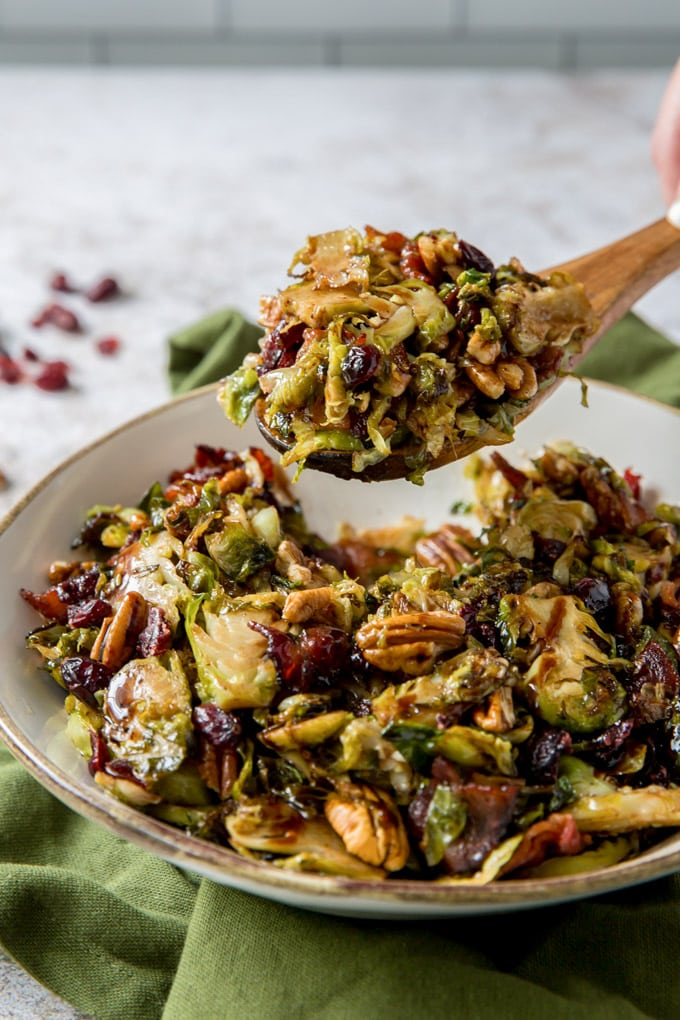 Brussels Sprouts salad on a wooden spoon held above a bowl