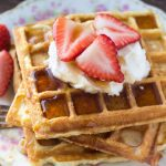 A stack of fluffy buttermilk waffles topped with whipped cream and drizzled in maple syrup is the perfect recipe for brunch. Learn all the tricks to fluffy waffles every time.
