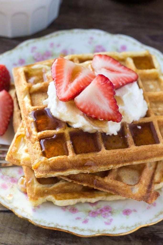A stack of fluffy homemade waffles topped with whipped cream, strawberries and drizzled in maple syrup is the perfect recipe for brunch. Learn all the tricks to fluffy waffles every time.