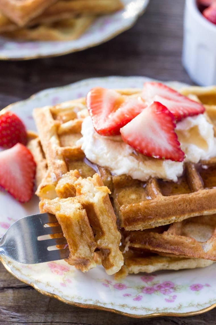 A stack of fluffy buttermilk waffles with a bite taken out.