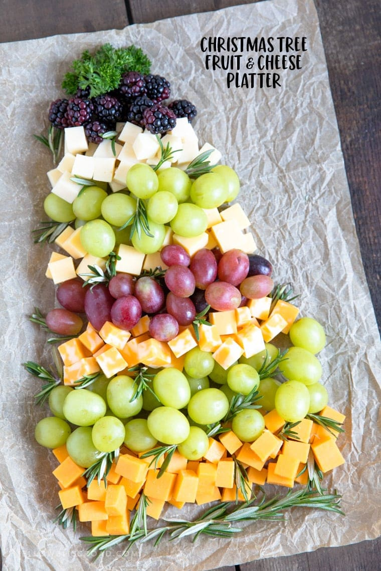 Fruit and cheese layered on a cutting board forming a christmas tree.