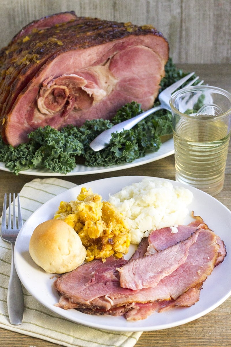 A plate with sliced baked ham, mashed potatoes, cornbread and a roll.
