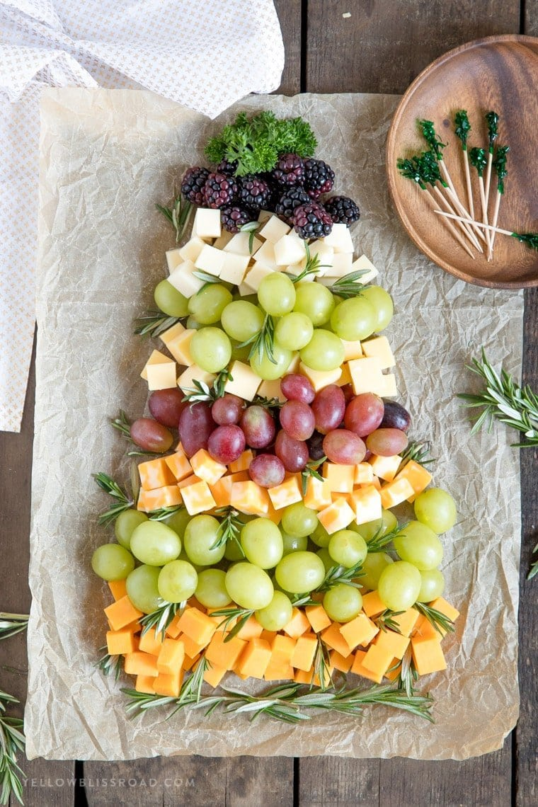 An overhead view of grapes, berries and cheese in the shape of a Christmas tree