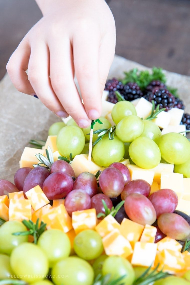 A child's hand reaching in to grab a piece of cheese from a fruit and cheese platter