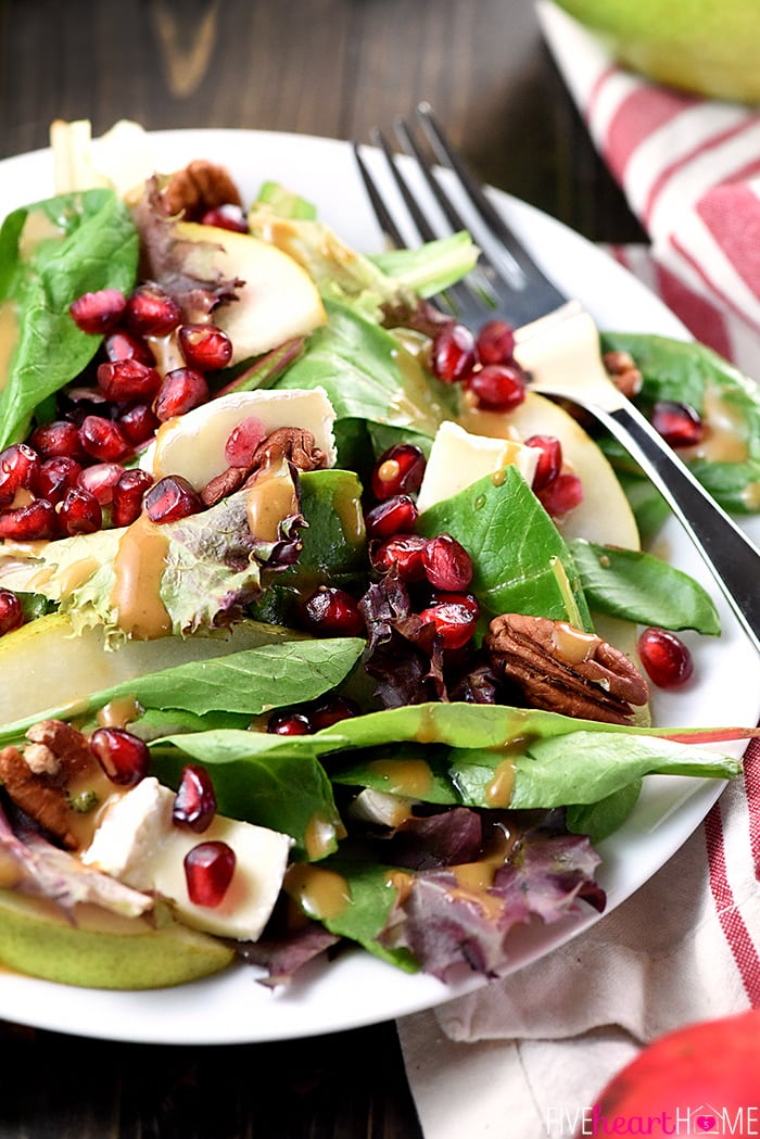 A plate of salad with pomegranate seeds