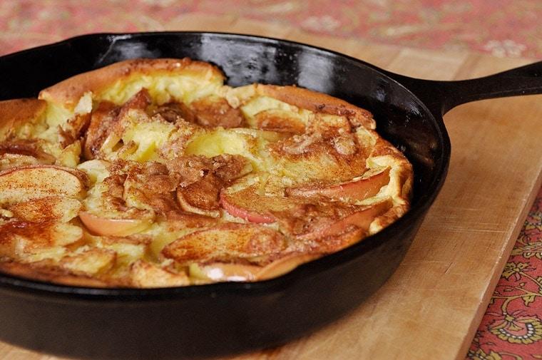 A cast iron pan with Dutch Baby Apple Pancake