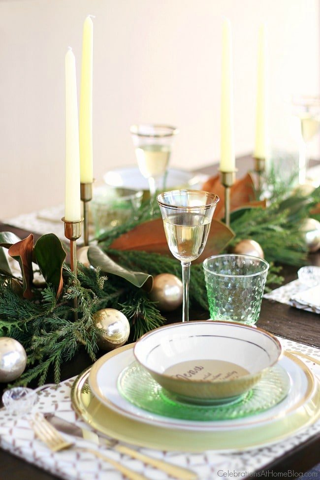 A decorated table with wine glasses, dishes, greenery, and candles