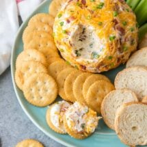 bacon cheddar cheeseball with crackers on a blue plate
