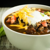 Healthy Turkey chili ready to eat in a white bowl topped with sour cream, cheese and tomatoes.