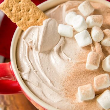 Cup filled with Hot Chocolate Dip with marshmallows and a graham cracker
