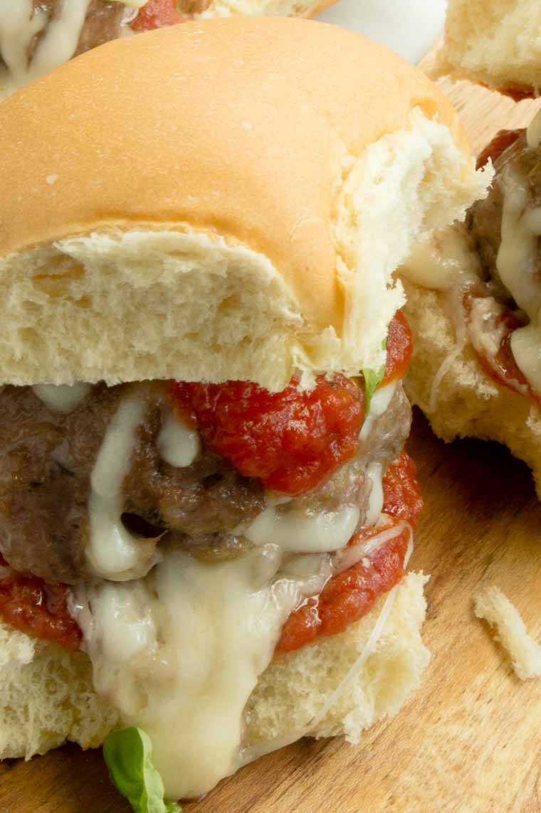These Italian Meatball Sliders will delight all of your game day party goers!  Juicy, cheesy filled meatballs slathered in melted Mozzarella drizzled with a tangy Italian Marinara sauce.