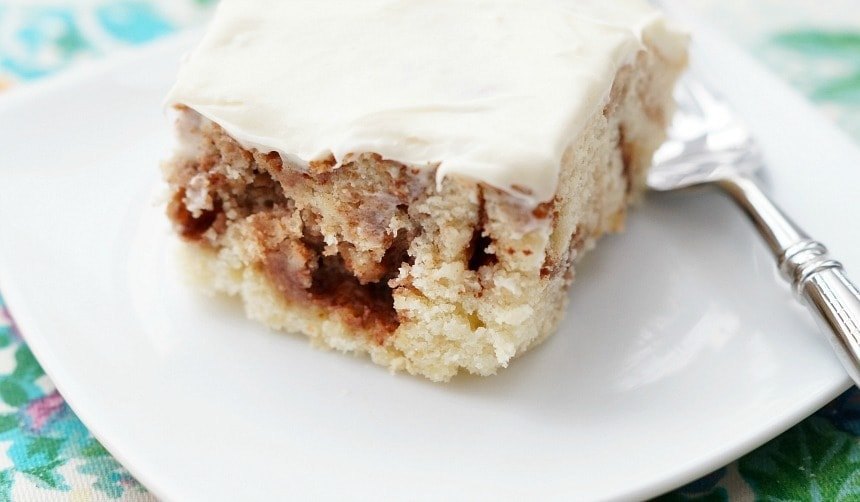 A slice of cinnamon roll cake with cream cheese frosting