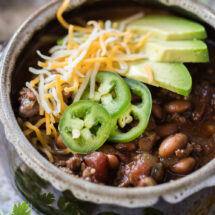 A bowl of chili with avocado slices, cheese, and jalapenos