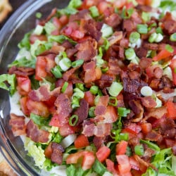 BLT dip in a glass pie dish with lettuce, green onions and bacon and tomatoes