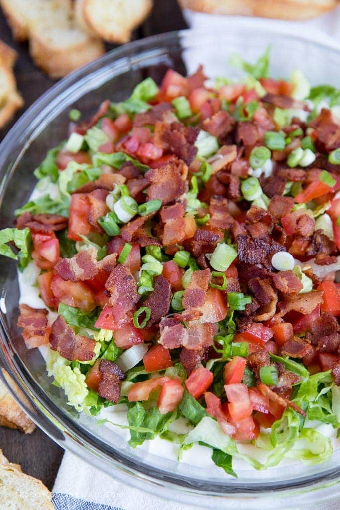 A clear glass pie plate filled with bacon lettuce and tomato and cream cheese dip