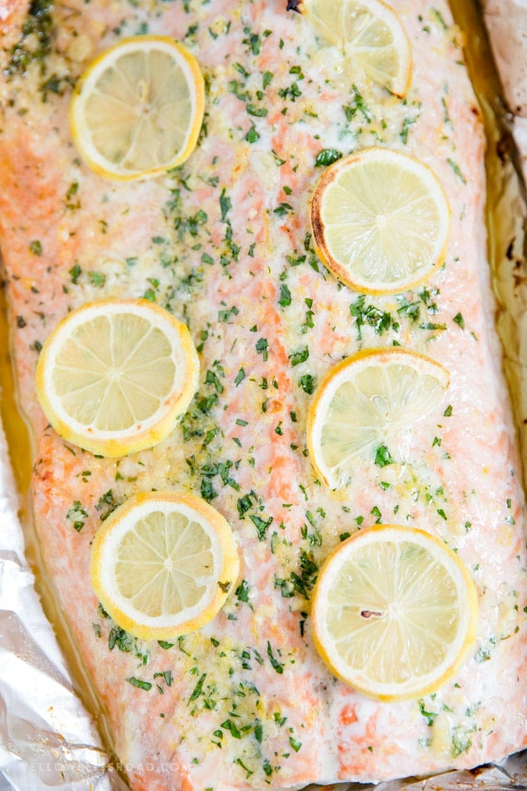 Piece of baked salmon covered with garlic butter and lemons