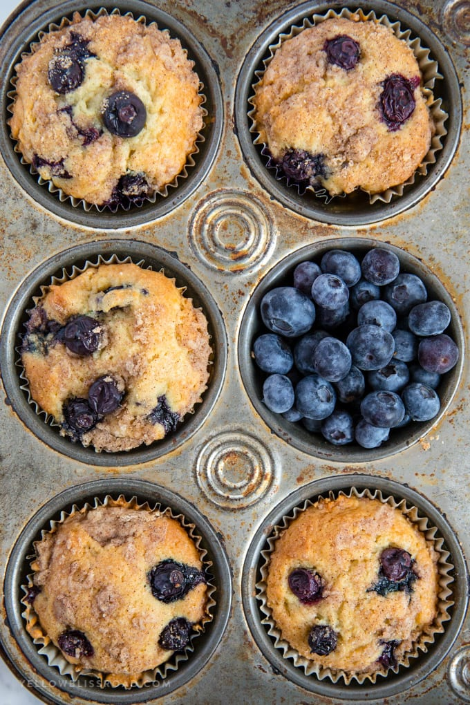 Blueberry Sour Cream Coffee Cake Muffins close up in a muffin tin full of blueberries