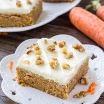 A slice of moist, chewy carrot cake bars with cream cheese frosting and chopped walnuts.