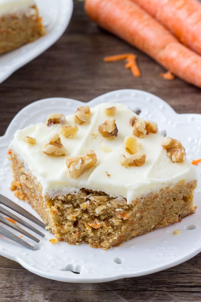 A slice of carrot cake bars with cream cheese frosting with a bite taken out.