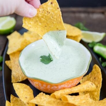 A chip dipping into a bowl of jalapeno ranch dip