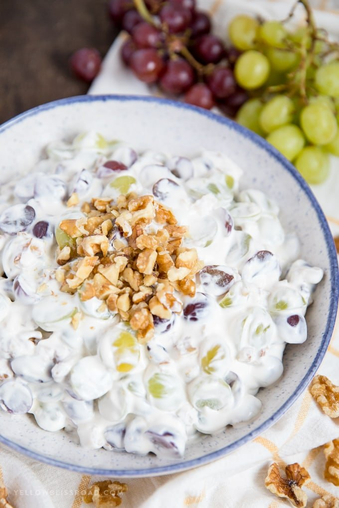 This Creamy Grape Salad with walnuts in a bowl with vines of grapes on the side