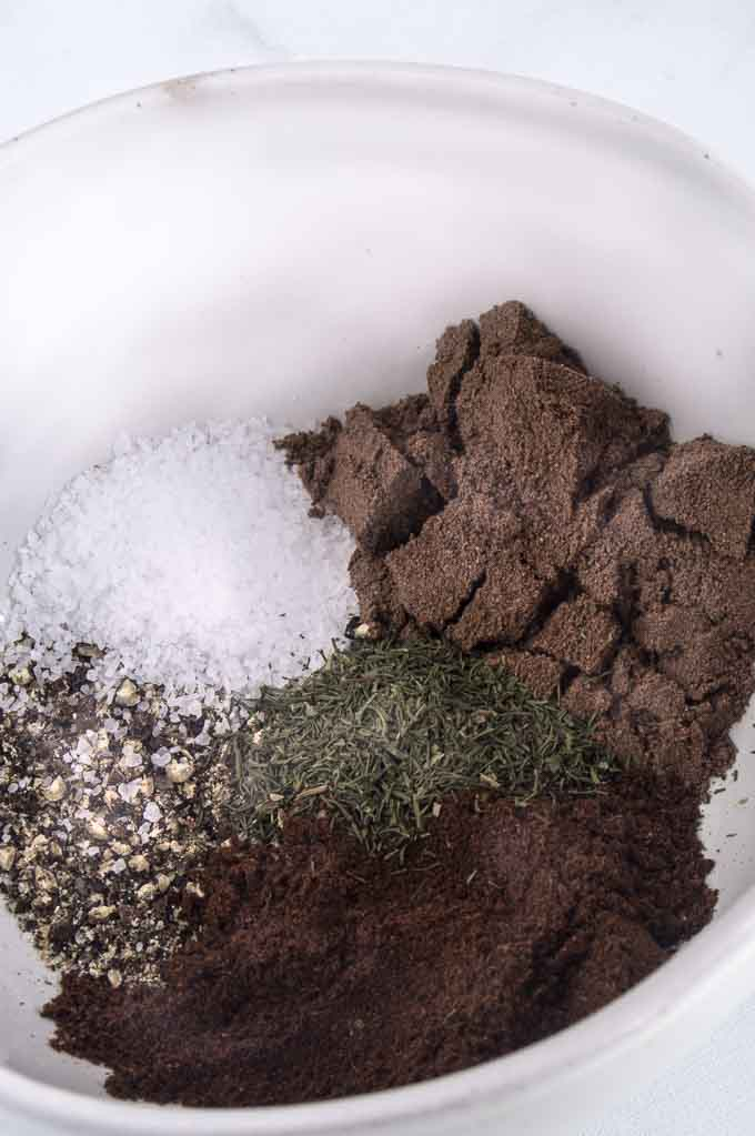 Close up of the jerk chicken spices needed: cloves, allspice, salt, pepper, thyme