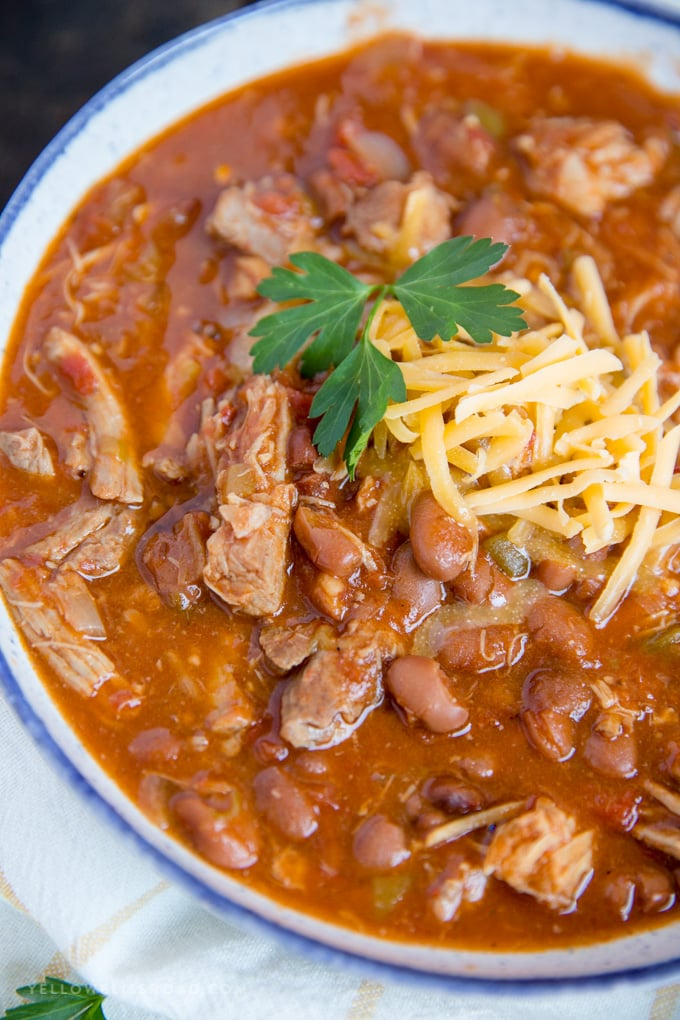 Slow Cooker Pulled Pork Chili with cheese and parsley garnish