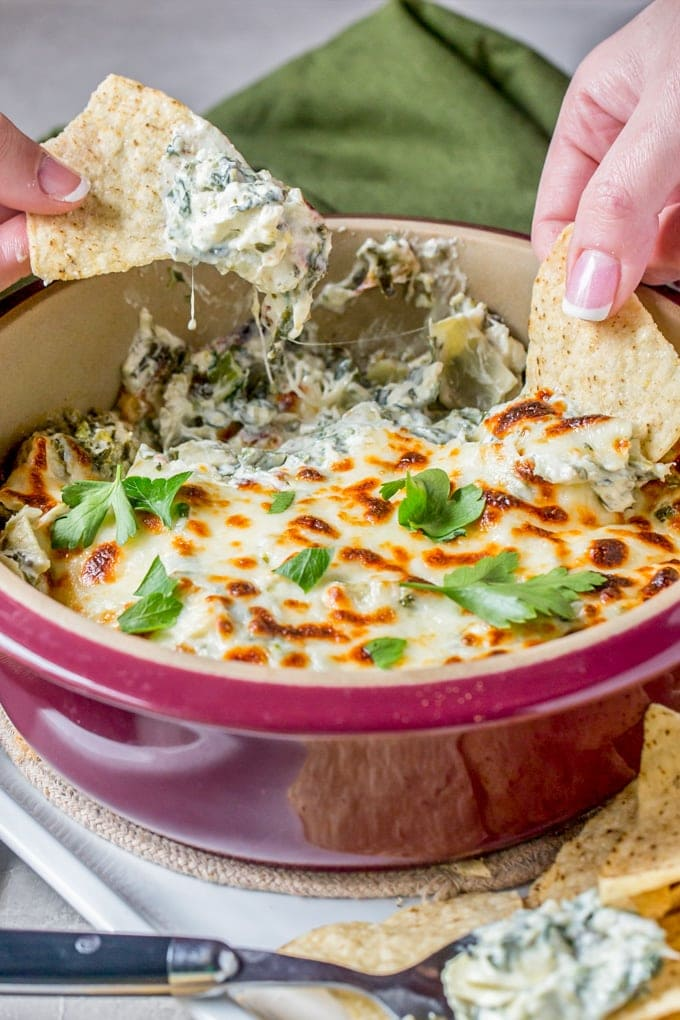 Two hands dipping tortilla chips into a pan of spinach artichoke dip.