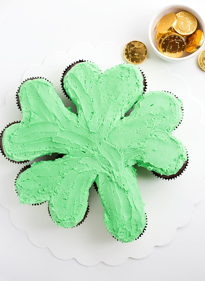 Green frosted cupcakes on a white cake board in the shape of a shamrock