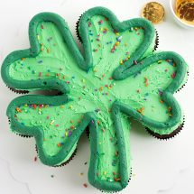 Green frosted cupcakes on a white cake board in the shape of a shamrock with a dark green outlining the shamrock and rainbow sprinkles on top