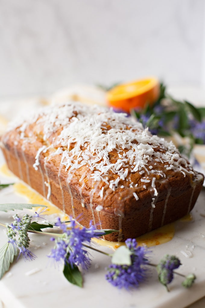 Coconut Banana Bread with Orange Glaze and shredded coconut on top. Perfect for Easter or Mother's Day!