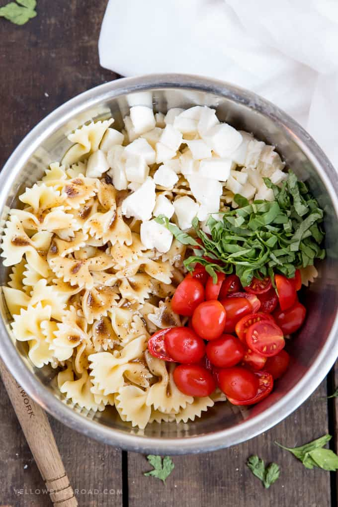 Ingredients for making Caprese Pasta Salad in a bowl with tomatoes, mozzarella cheese, basil and pasta